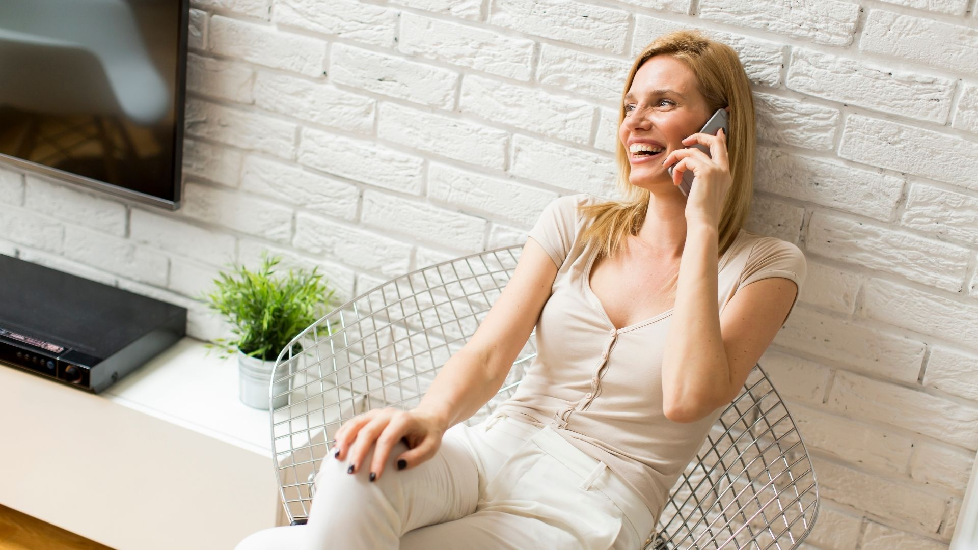 Femme joyeuse discutant au téléphone dans son salon