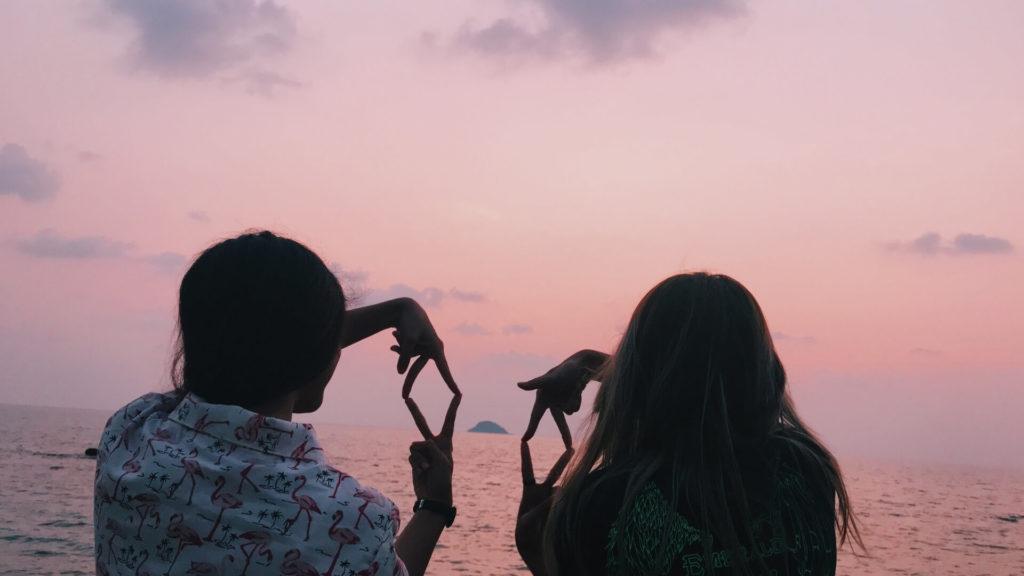 Deux amies devant un coucher de soleil rose sur la plage