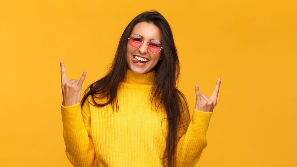 Jeune femme riant et levant ses doigts habillée en jaune avec des lunettes jaunes sur un fond de même couleur