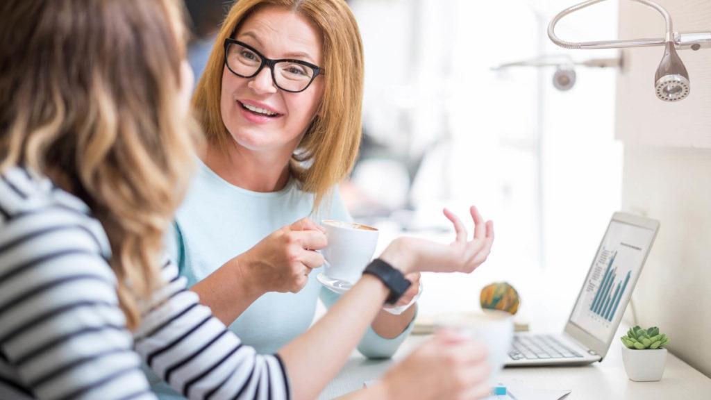 Deux collègues de travail femmes qui discutent joyeusement à leur poste de travail en buvant un café
