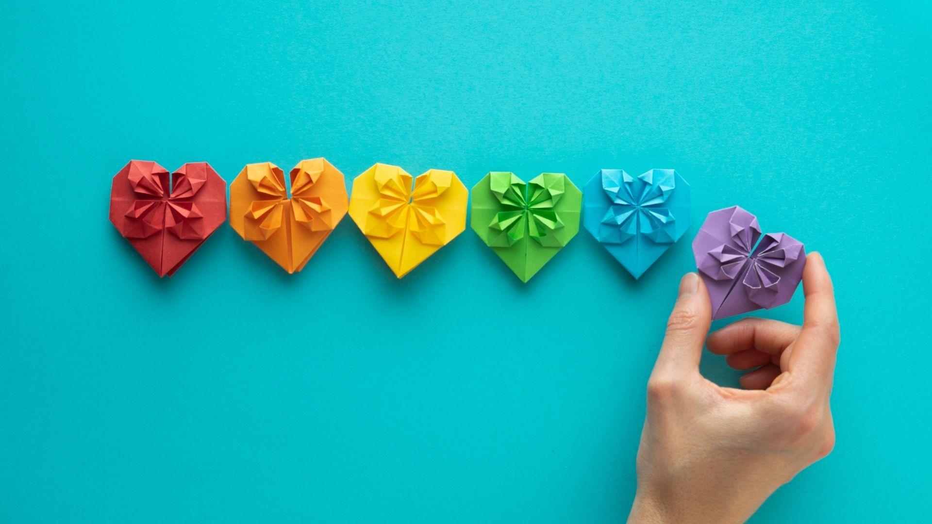 Main d'une personne déposant des origamis en forme de coeurs, aux couleurs du mouvement LGBT, sur un fond de papier turquoise.