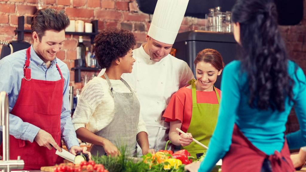 Plusieurs personnes joyeuses qui prennent un cours de cuisine avec un chef