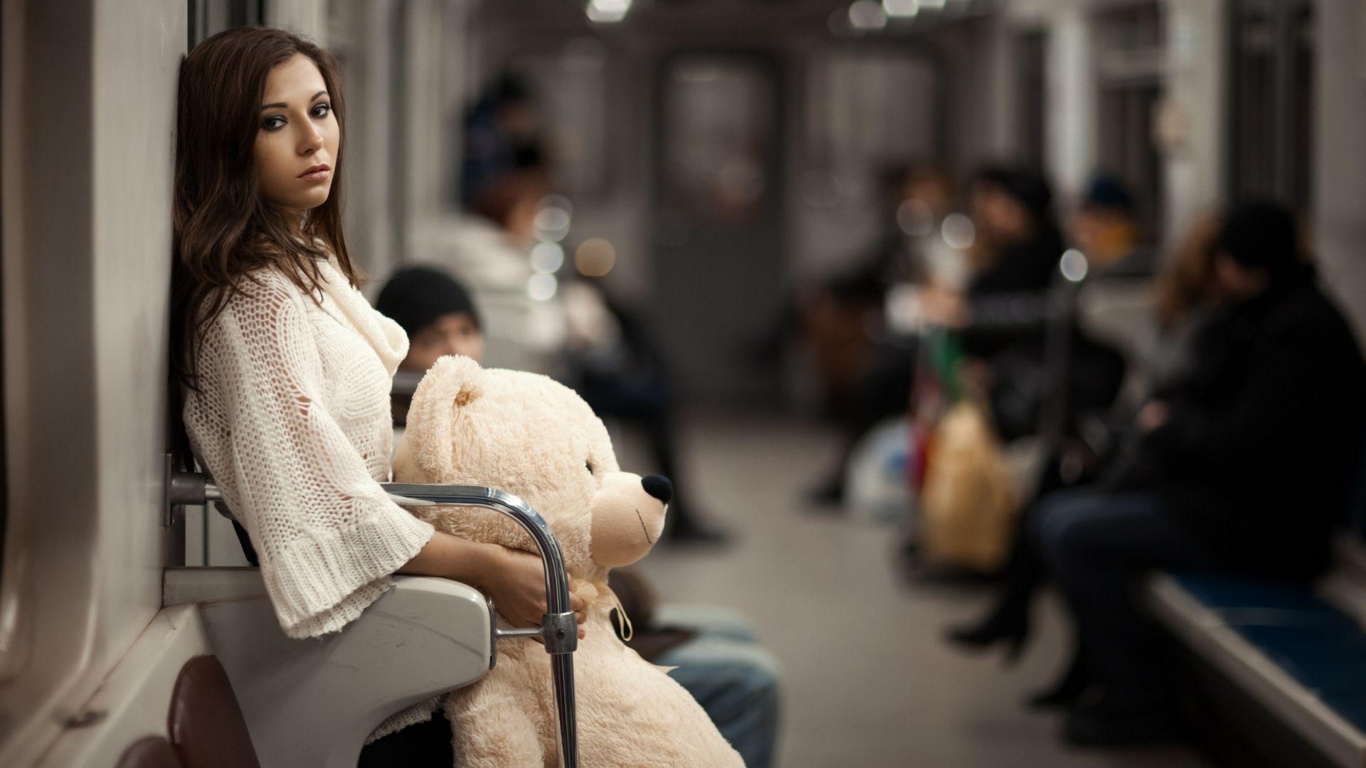 Jeune fille à l'air triste, debout dans un métro bondé, tenant une peluche géante en forme de nounours contre elle