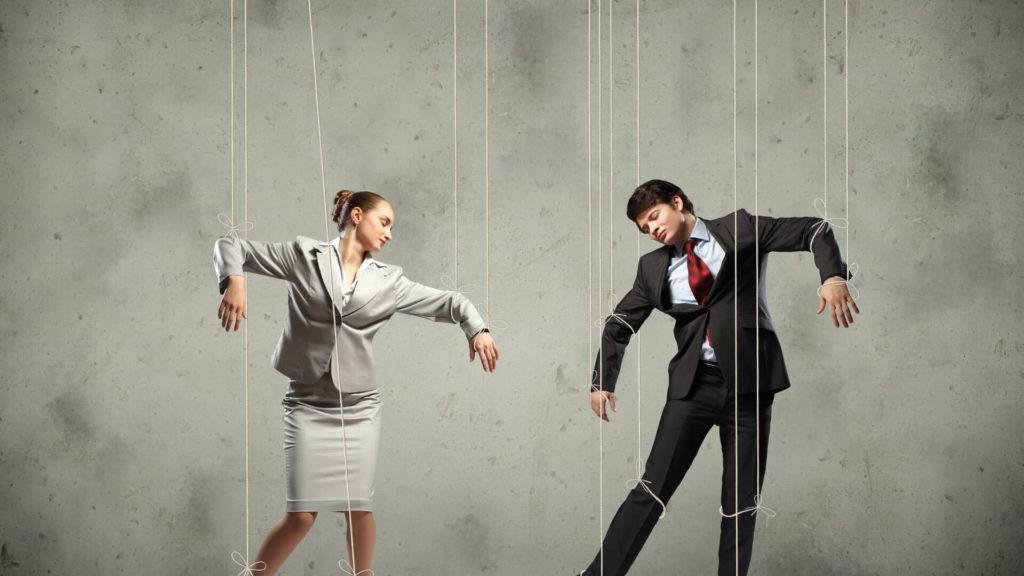 Un homme et une femme en costume et tailleur attachées au poignet par des fils comme des marionnettes