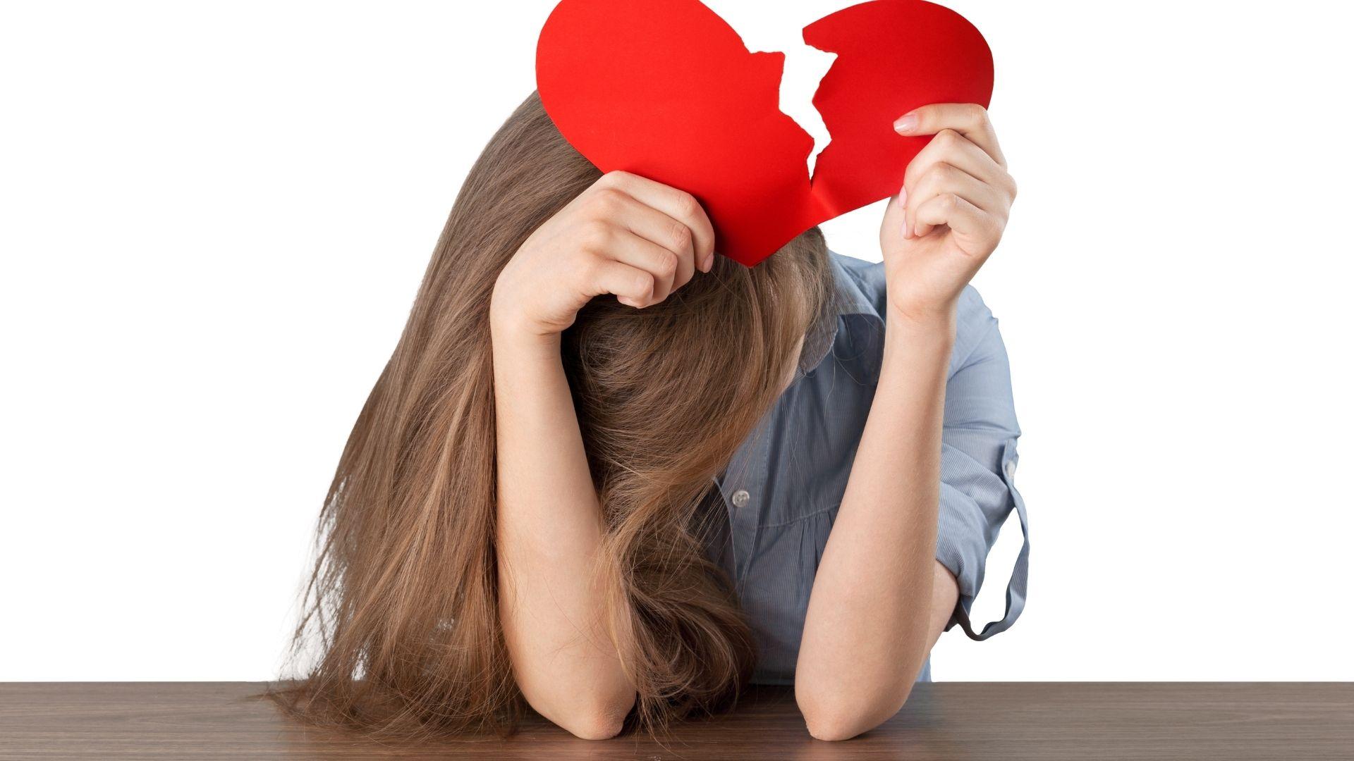 Jeune fille accoudée sur une table, se cachant le visage dans les bras et brandissant un coeur en papier brisé en deux