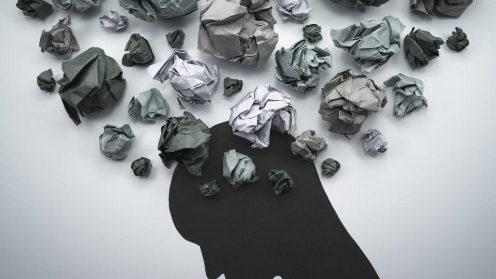 Silhouette d'une tête humaine en papier avec des boules de papier froissé de couleurs noire qui représentent des pensées anxieuses