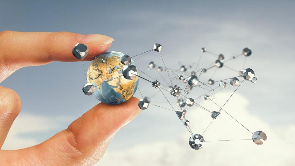 Main humaine qui tient une planète miniature entre ses doigts autour de laquelle circulent des planètes représentant les réseaux sociaux virtuels