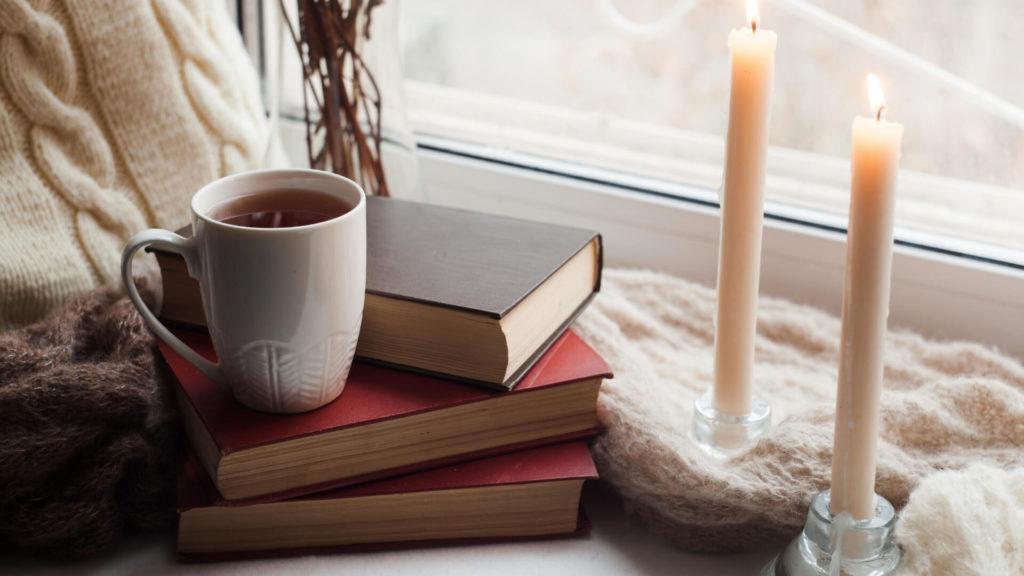 Thé, bougies et livre posés sur une table