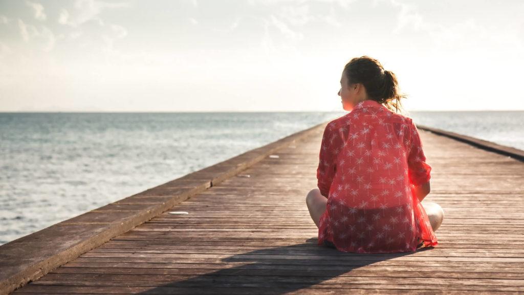 Femme seule assise sur un ponton face à la mer