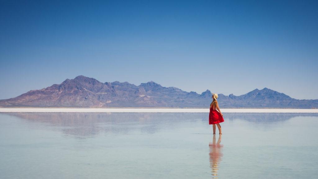 Jeune femme qui danse dans un lac bleuté transparent avec en arrière-plan de montagnes